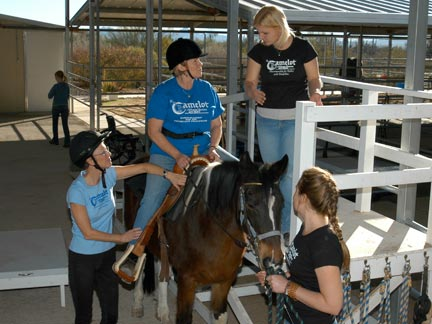 Mounted student next to ramp with instructor and volunteers