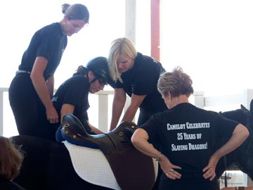 instructors and volunteer helping a student mount