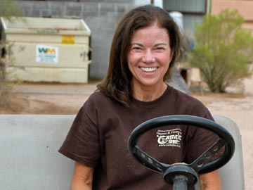 smiling volunteer in golf cart