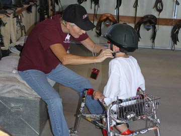 volunteer helping young student with helmet