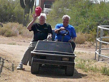 two male volunteers driving golf cart