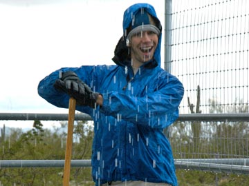 smiling young man in rain, mucking stalls
