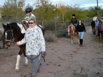 volunteers leading students on trail ride