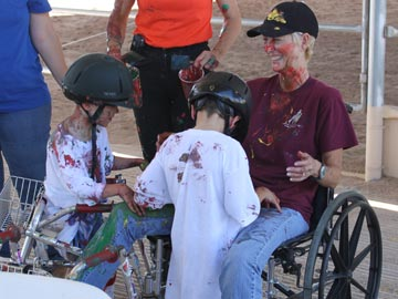 paint-splattered volunteer and 2 students