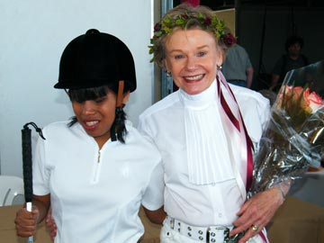 blind student in helmet standing with smiling volunteer holding flowers