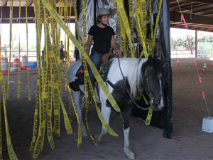 Clinic participant riding horse through strands of caution tape
