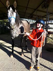 young male student leading Barbara in barn
