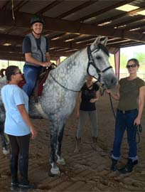 Barbara with adult male student riding in arena, volunteers and instructor standing nearby