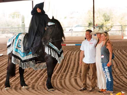 K2 wearing native Arab costume, ridden by woman in black hooded cape, standing next to sponsors in covered arena