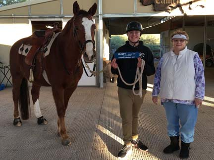 Young male student holding tacked-up Rusty in the breezeway, adult female volunteer standing next to them