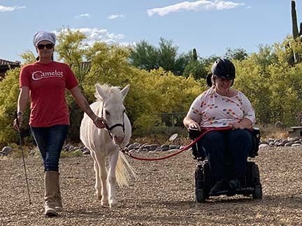 Small white donkey being led by woman in power wheelchair